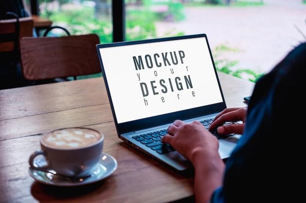 コーヒーショップでラップトップを使用して入力するビジネス女性のモックアップ画像。