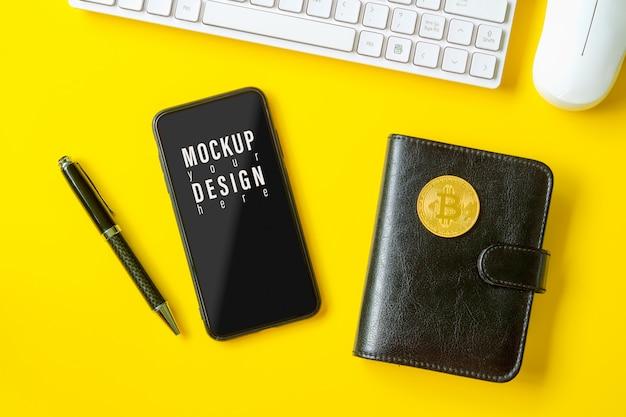 Макет мобильного телефона на желтом столе с биткойнами на ноутбуке.