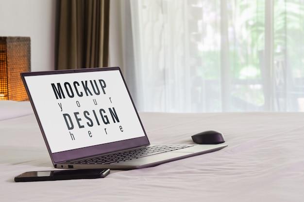 ベッドの上のモックアップノートパソコン
