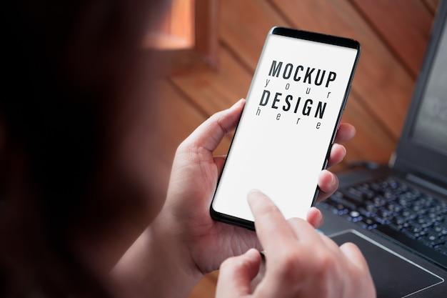 スマートフォンのモックアップ画面、保持しているビジネス女性の画像を閉じるし、スマートフォンをタッチ