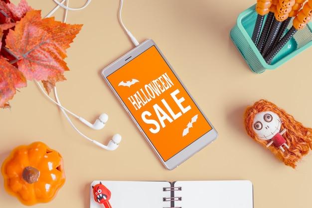 。ハロウィーンアクセサリーとオフィスデスクテーブル上のスマートフォンの平面図。