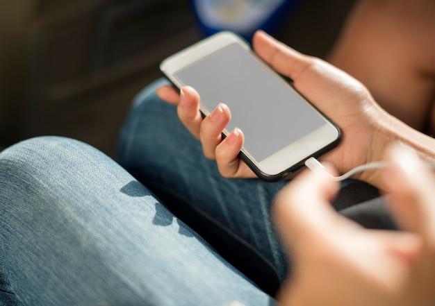 携帯電話を充電する手のクローズアップ