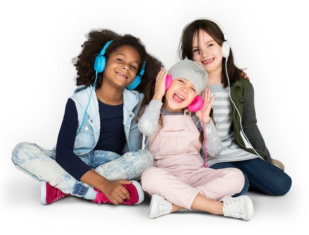 小さな女の子のグループスタジオ笑顔のヘッドフォンと冬の服を着て