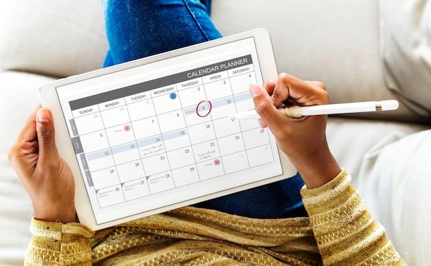 Женщина, проверяющая календарь на цифровой планшете