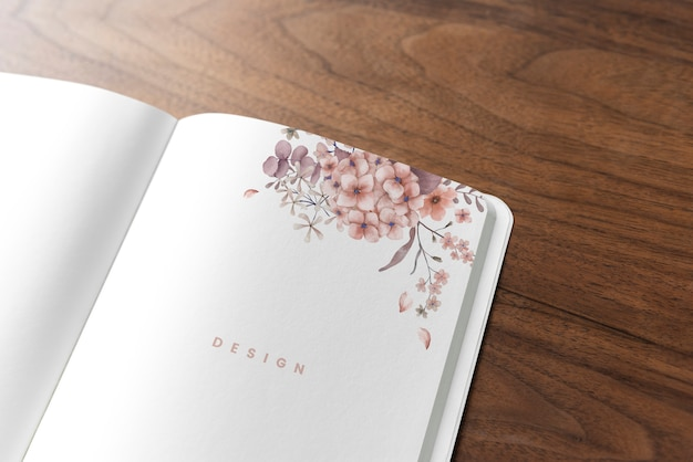 木製のテーブル上の花のノートブックモックアップ