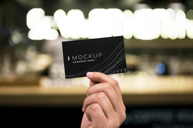 Женская рука держит черный макет визитной карточки