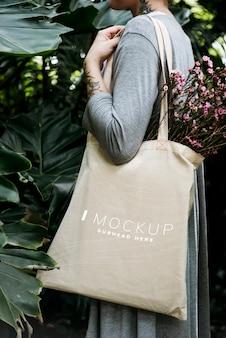 花とトートバッグのモックアップを運ぶ女性