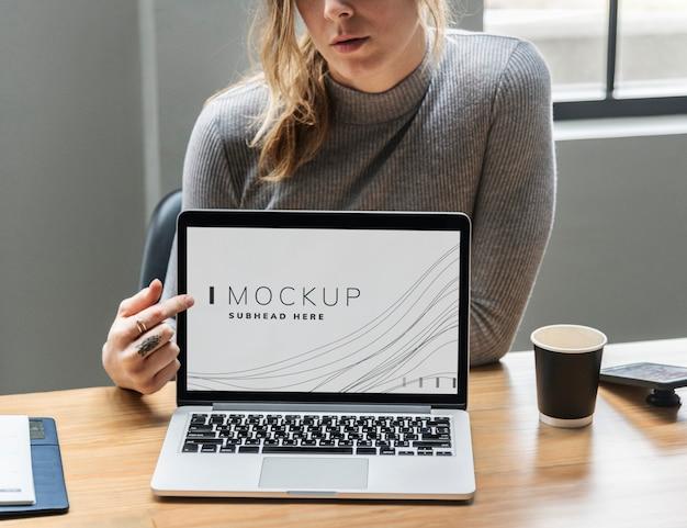 ノートパソコンの画面のモックアップを示す女性