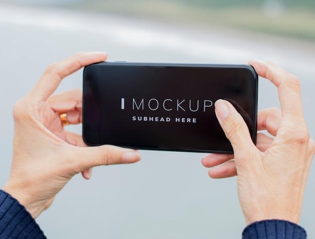 屋外の携帯電話のモックアップを保持している女性