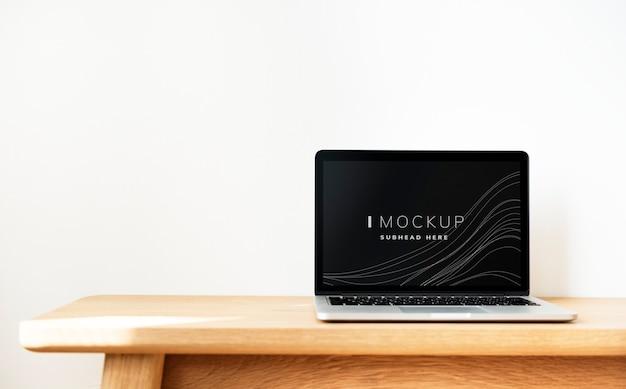 木製のテーブルの上のノートパソコンの画面のモックアップ