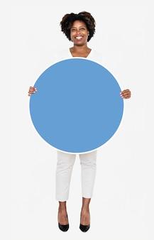Жизнерадостная коммерсантка держа голубую круглую доску