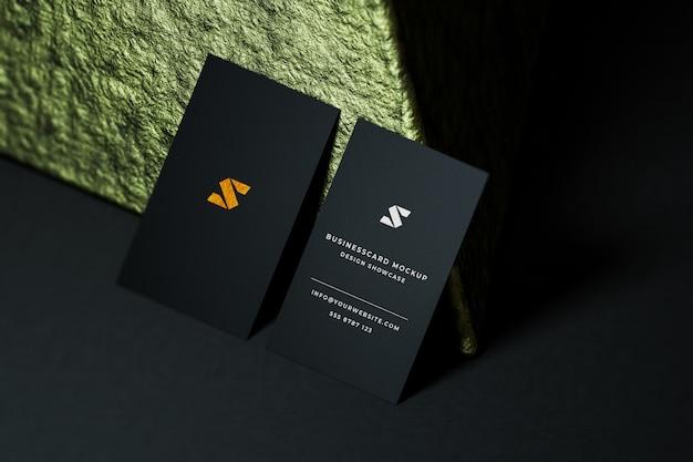 ラグジュアリーゴールデン名刺モックアップ。ゴールド黒の背景にカード。