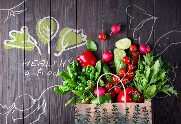 木製の表面に野菜がいっぱい食料品袋