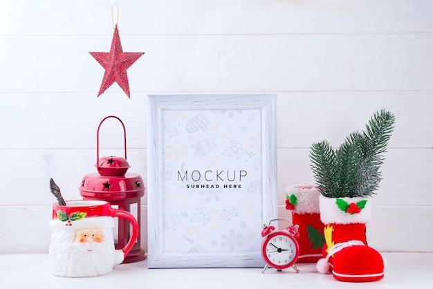 白い木製の背景に白いフレーム、赤いランタン、サンタクロースのカップとモックアップの写真