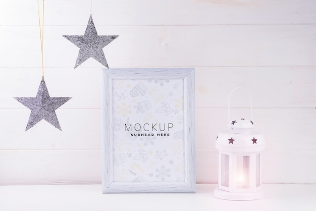 白いフレーム、星、白い木製の背景にランタンとモックアップの写真