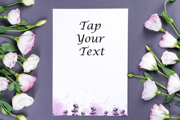 コピースペースを持つ灰色の紙に空の紙と花トルコギキョウ。