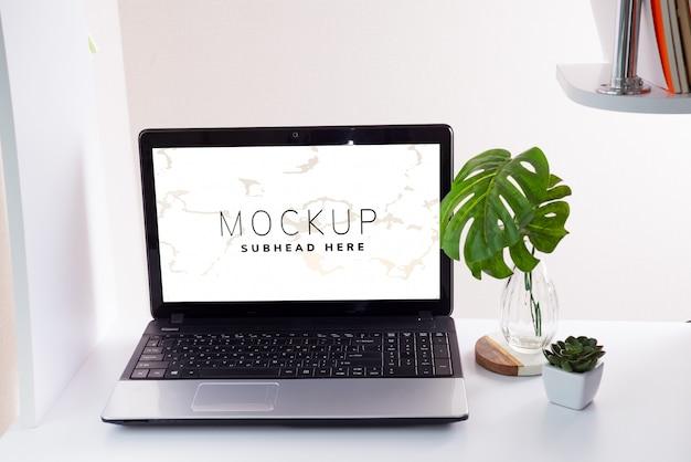 Рабочее место с ноутбуком и листьями монстера