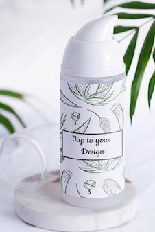 常緑のヤシの葉で大理石のテーブルに白いシェービングフォームまたはクリーニングローションボトルモックアップ