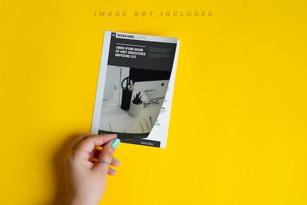 女性の手は開いているモックアップのパンフレットまたはカタログ
