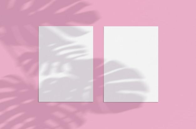 モンステラとピンクの空白の白い垂直紙シートカードモックアップは、影のオーバーレイを残します。モダンでスタイリッシュなグリーティングカードのモックアップ