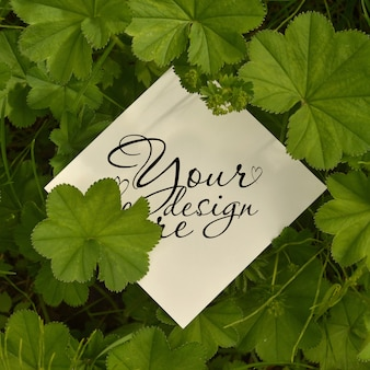 紙カードと葉の正方形のモックアップ。広告カードまたは招待状の場合は空白