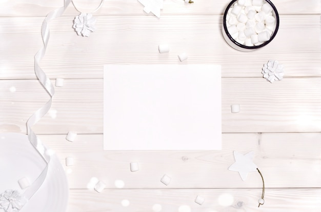 クリスマスカードモックアップと木製テーブルの上の白い装飾