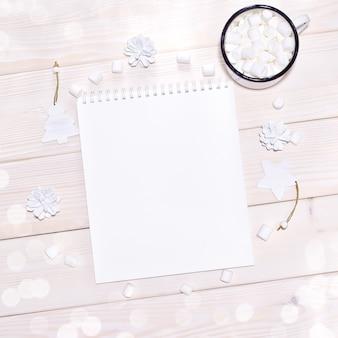 木製テーブルの上の白い装飾とメモ帳のモックアップ