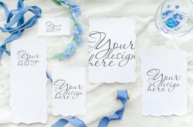 紙カードセットと青いリボンと花輪の結婚式フラットレイアウトモックアップ
