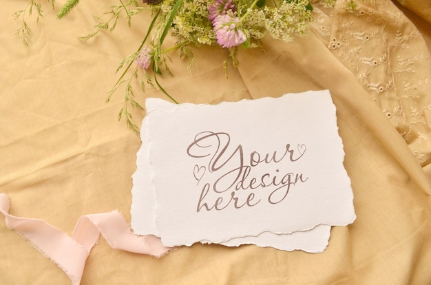 紙カードと野生の花の結婚式のフラットレイアウトモックアップ