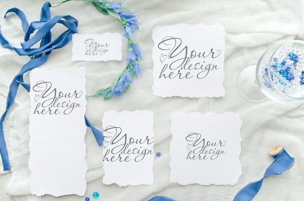 シルクリボン、クリスタル、花嫁の花輪で飾られた青い結婚式招待状セットモックアップ