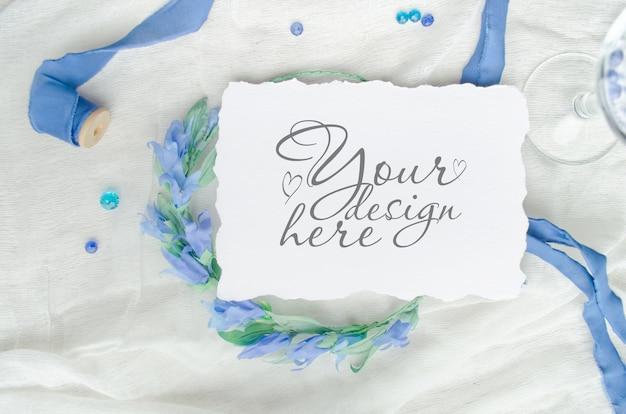 シルクリボン、クリスタル、花嫁の花輪で飾られた青い結婚式招待状のモックアップ