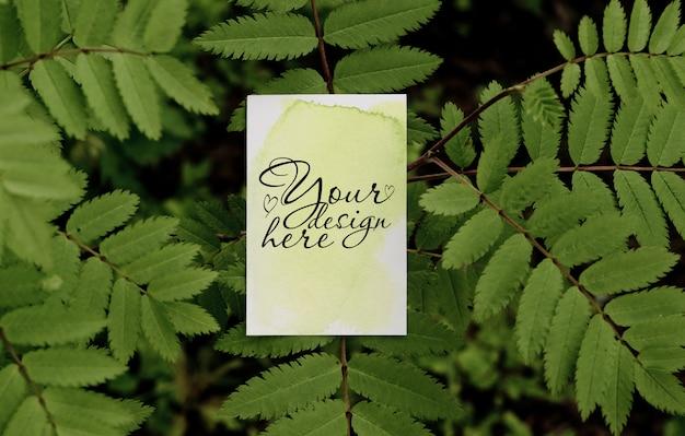 葉の木の背景に名刺モックアップ