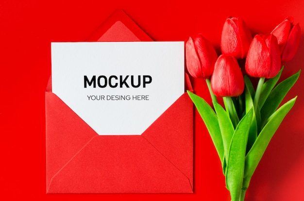 Красный конверт с пустой белой бумаги и букет из тюльпанов.