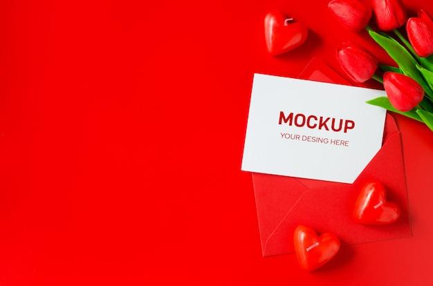 Красный конверт с чистого листа, букет тюльпанов и свечи в форме сердца.