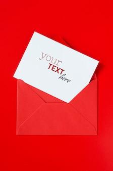 空白の白い紙と赤い封筒。バレンタインデーのラブレターのモックアップ。
