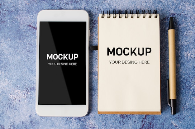 空のノートと青い机の上のスマートフォン。メモ帳で空の紙。