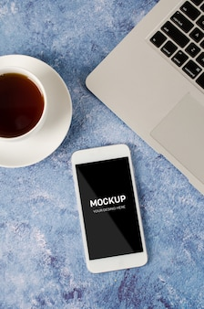 ノートパソコンと紅茶のカップとオフィスの机の上の黒い空白の画面と白いスマートフォン。電話のモックアップ。