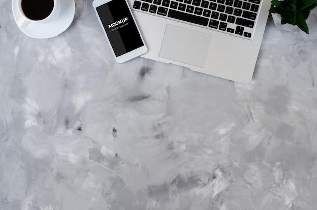 Белый смартфон с черным пустым экраном на офисном столе с ноутбуком и чашкой кофе. макет телефона.