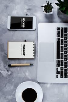 ノートパソコンとコーヒーカップとオフィスの机の上の黒い空白の画面と白いスマートフォン。電話のモックアップ。