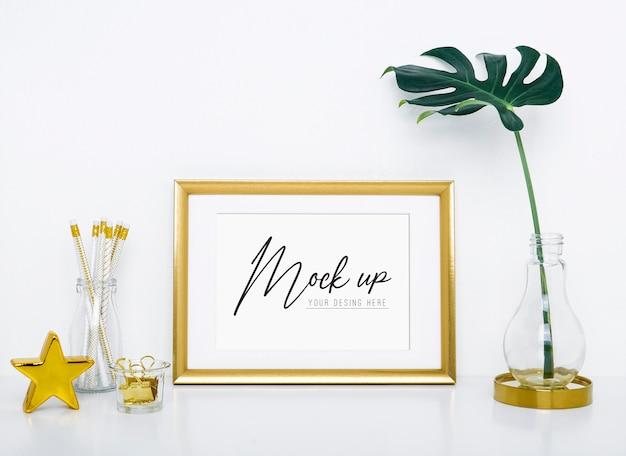 花瓶と室内装飾用のオブジェクトを備えたゴールドフレームモックアップ。