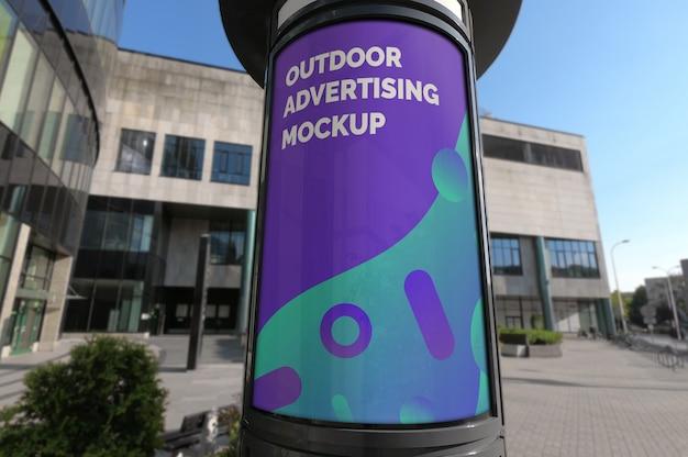 都市通りの舗装上の屋外の垂直広告ブースのモックアップ