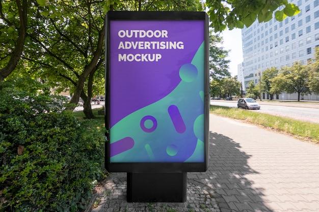 都市通りの舗装の上に立つ屋外の黒い垂直広告のモックアップ