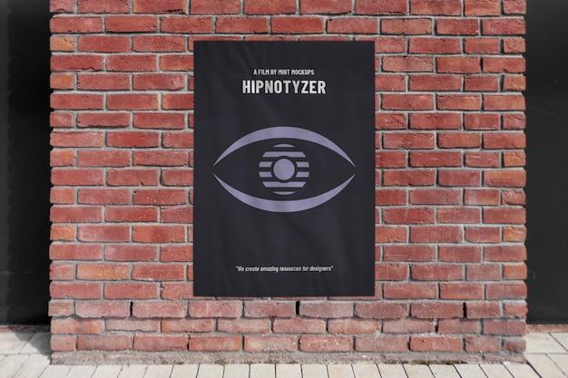 レンガ壁のファサードに屋外の垂直広告ポスターのモックアップ