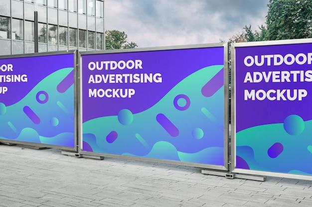 銀色の金属フェンスに広告する通り都市屋外の複数の水平看板バナーのモックアップ