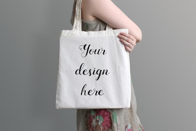 Молодая женщина, несущая экологическую хлопковую сумку, макет продукта