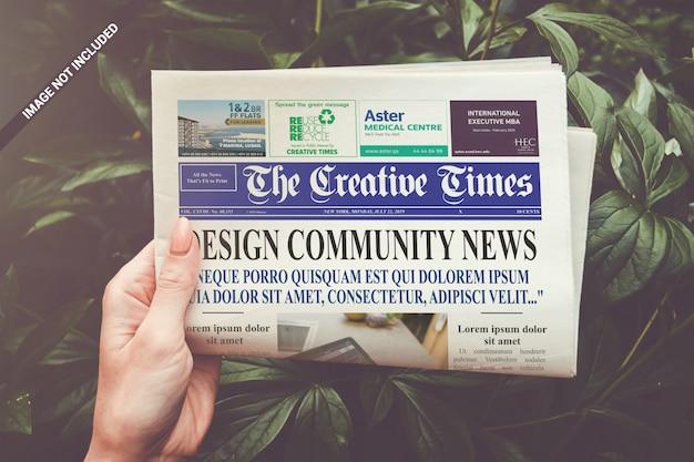 折り畳まれた新聞を手にモックアップ