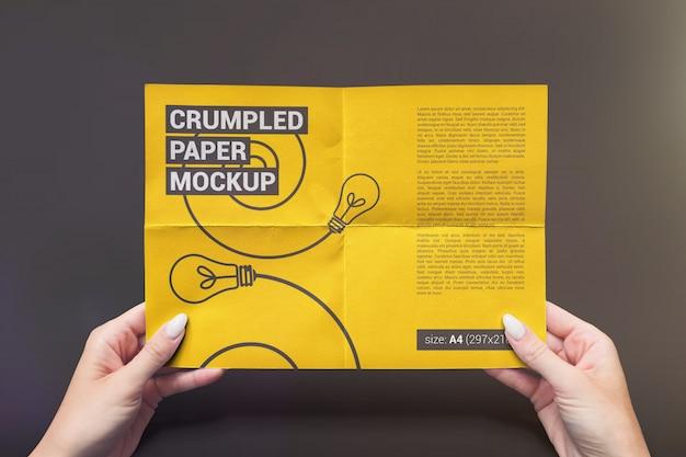 手のモックアップで折り畳まれた紙