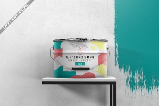 Ведро с краской на столе с расписной стеной