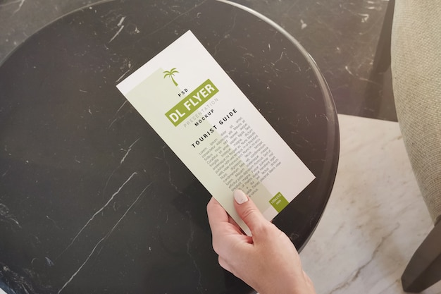 Рекламный флаер в руке над журнальным столиком макета