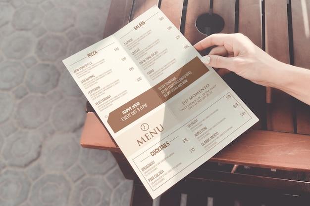 Девушка держит макет меню